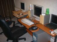 3台のパソコンと机が並んでいる。